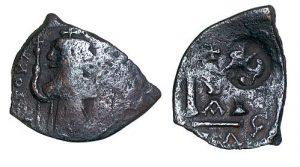 This piece of base metal was originally an unidentifiable older coin, cut into smaller parts, struck with the image of a Constans II (641-668) follis, then countermarked for reuse with the monogram of Constantine IV (668-685).