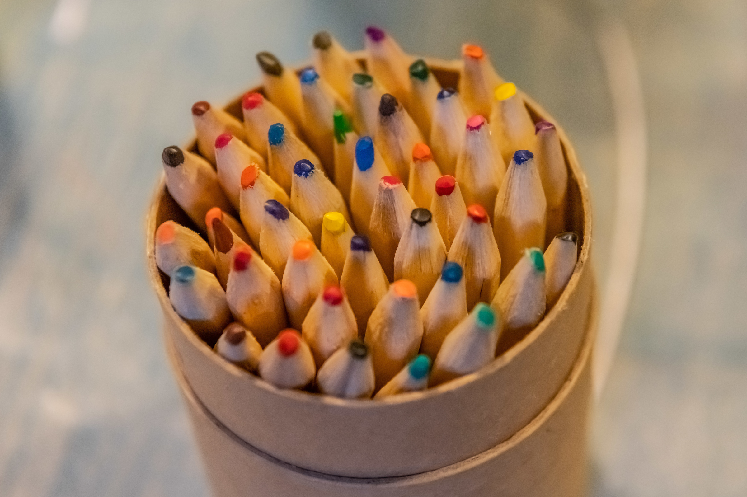 The tops of colourful pencils; they stand in a brown circular container.